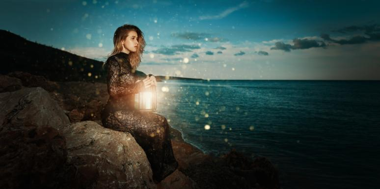 woman with lantern at night thinking of past life relationships