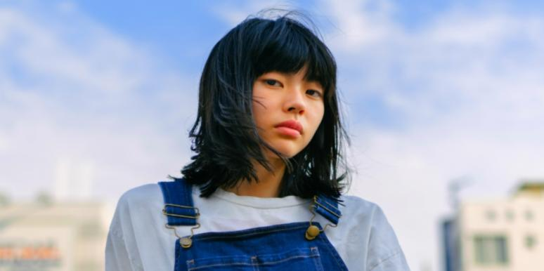 woman in overalls and bangs looking forward
