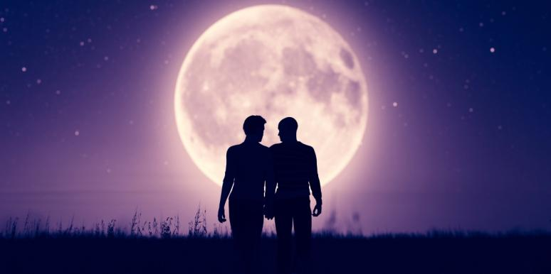 two men holding hands in front of the moon