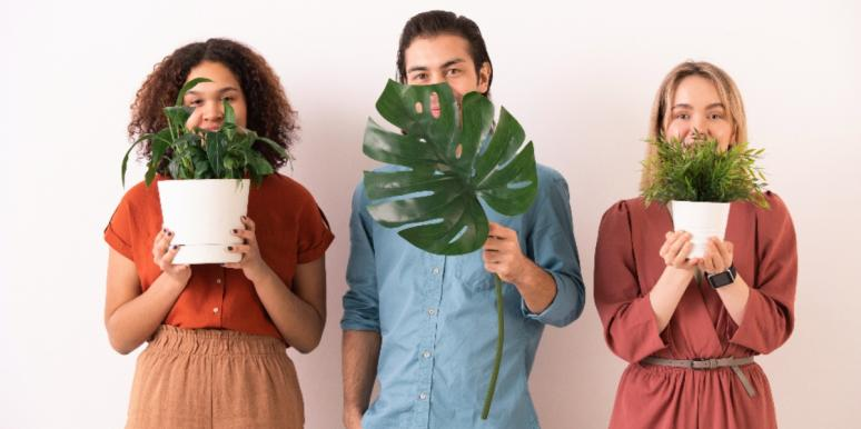 people holding up plants