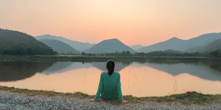 woman sitting by water