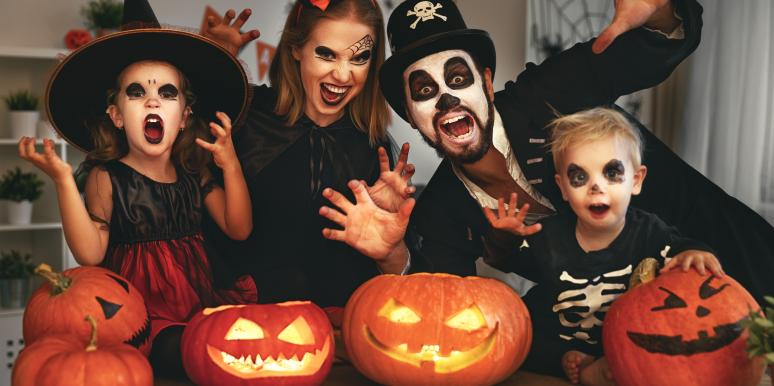 family in halloween costumes with pumpkins