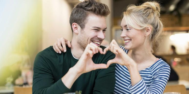 man and woman making heart with their hands