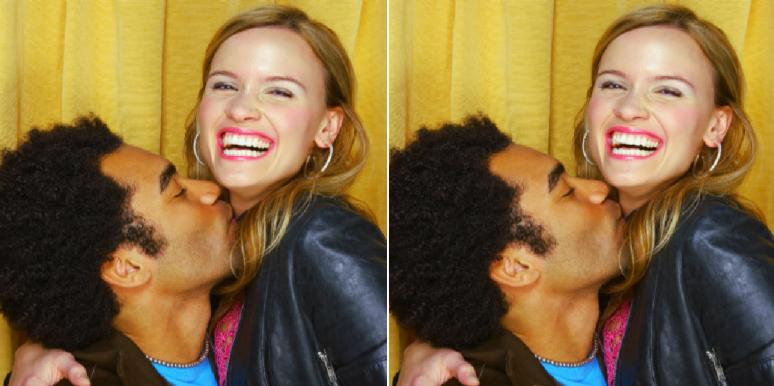 couple kissing and smiling in a photo booth