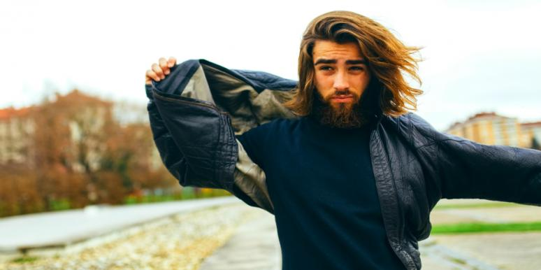 guy holding jacket in the wind