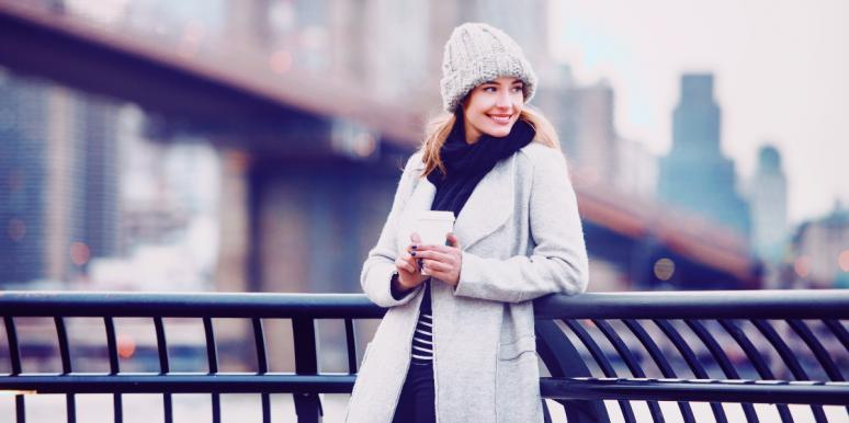 smiling woman in a white coat in city