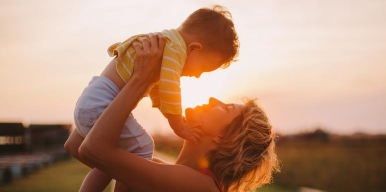 mother playing with son outside during sunset