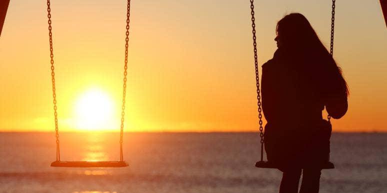 woman sitting swing sunset