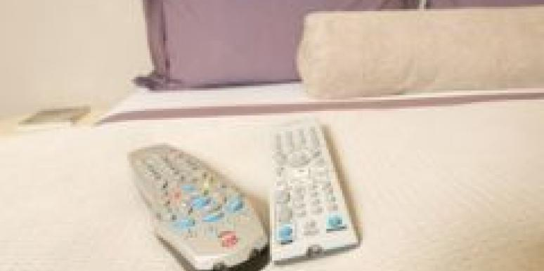 remote controls bed purple pillows