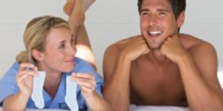 Man and woman in bed holding tiny socks