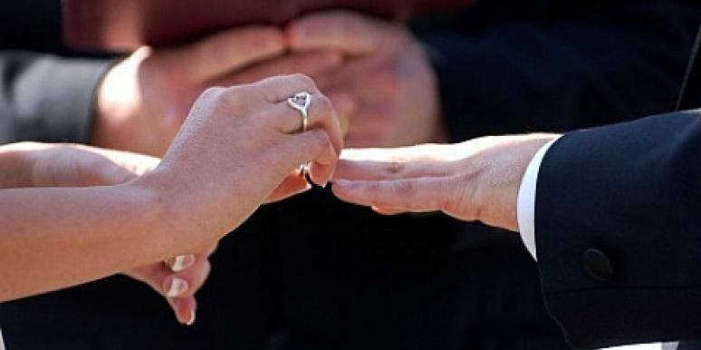 couple putting ring on finger in marriage ceremony
