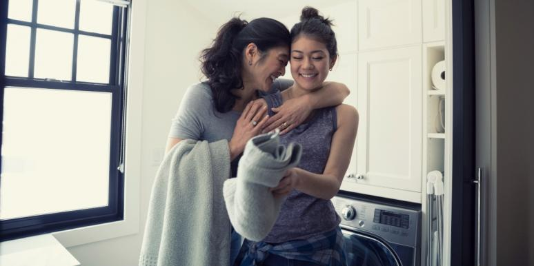 happy mom with daughter doing laundry