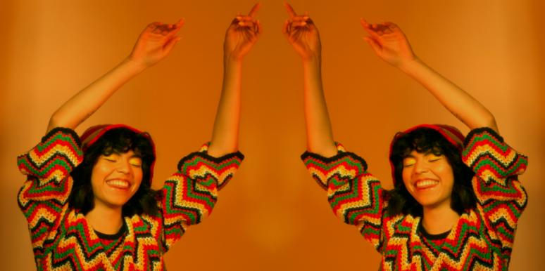 woman with her arms up in the air on orange background