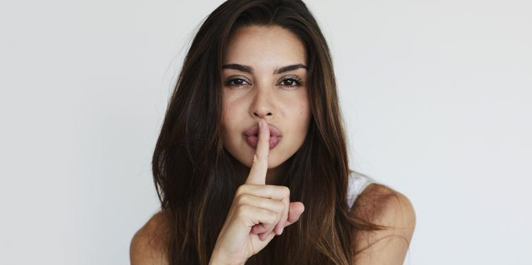 woman with finger on mouth shushing secret