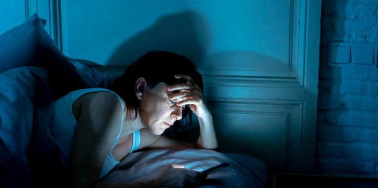 man in bed looking at phone nighttime