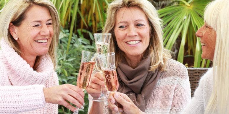 three older women toasting wine