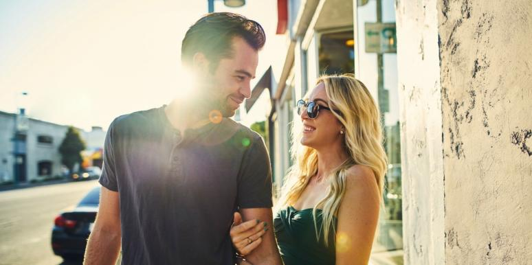 couple with lots of sexual tension flirts on the street, sun flare behind them