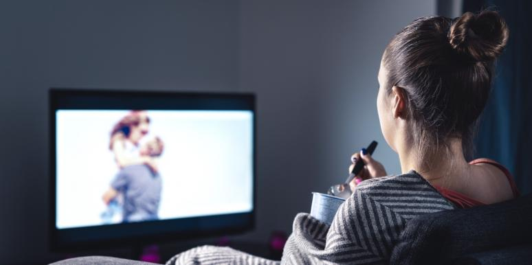 woman watching couple on tv and eating ice cream