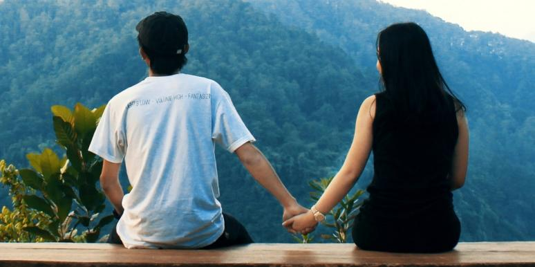 couple holding hands at overlook