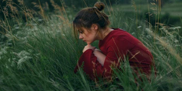 sad woman sitting in the grass