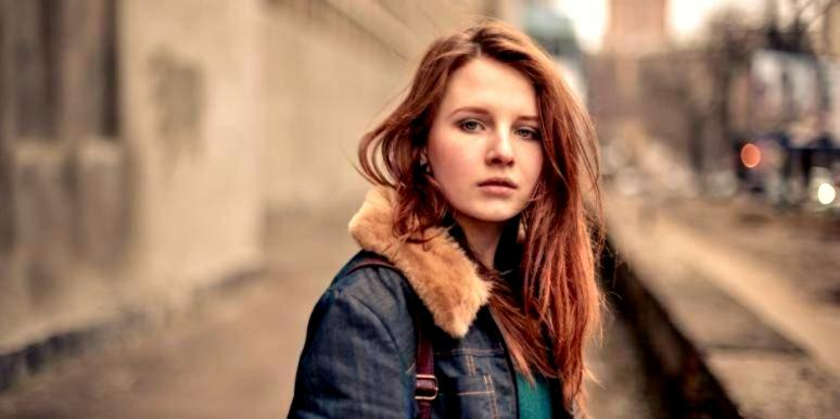 sad woman looking forward red hair jean jacket