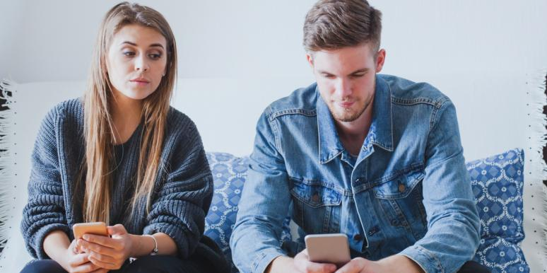 woman with trust issues glancing at man's phone