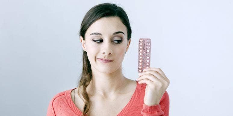 woman holding up birth control pills