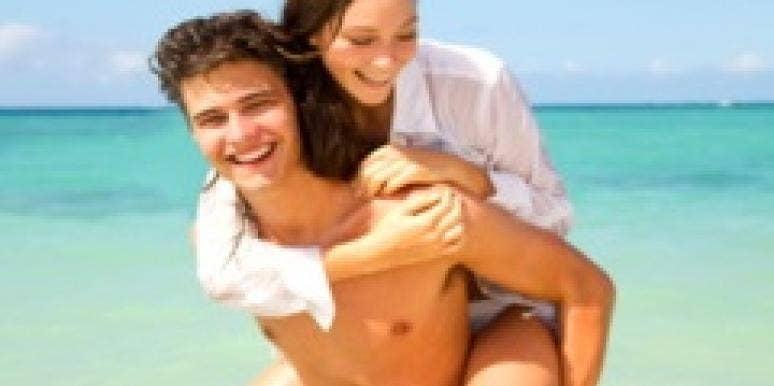 couple on the beach piggy back