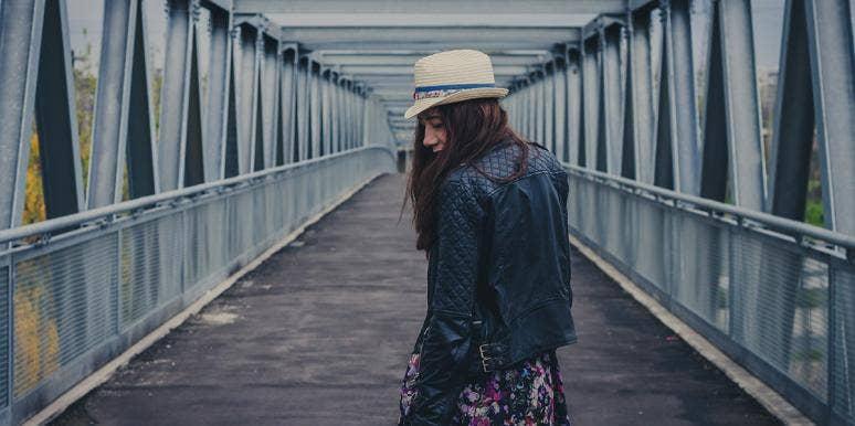woman on a bridge walking away