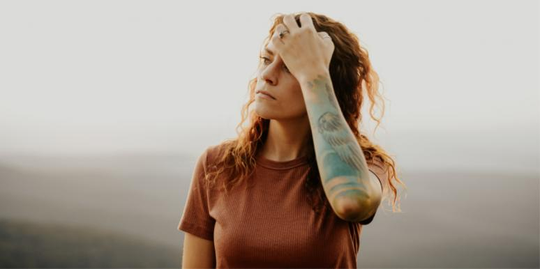 woman with tattoo with hand in hair