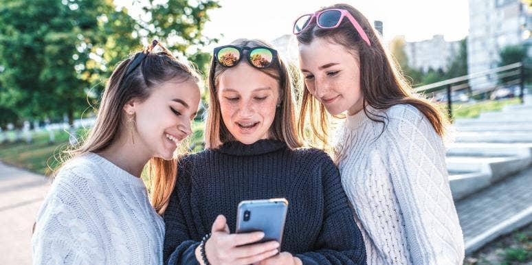three teenage girls looking at a smartphone