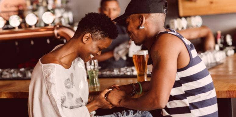 woman and man at bar holding hands