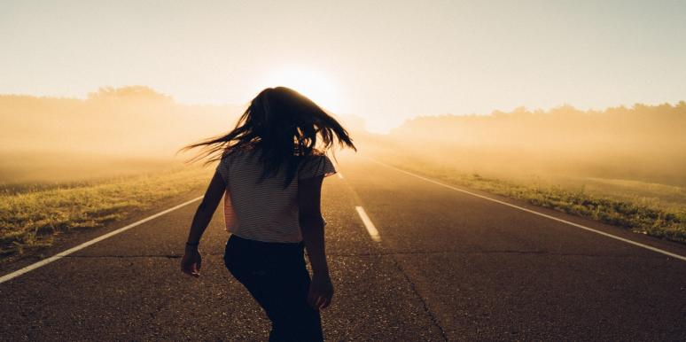 woman walking away desert road