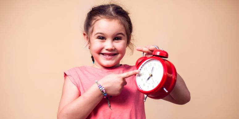 little girl pointing at a red clock