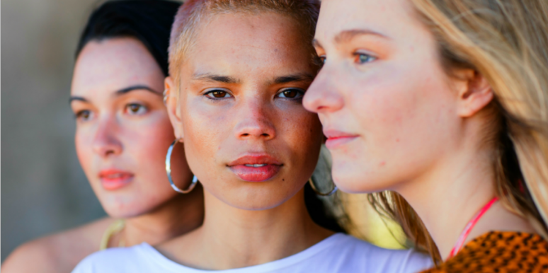 three young ladies, a pale brunette, a tawny blonde, and a pale blonde look into the camera or away wistfully, zoomed in closely.