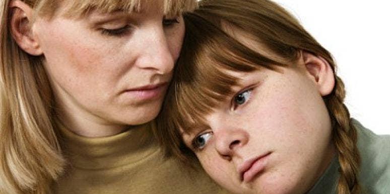 sad daughter leaning on mother's shoulder