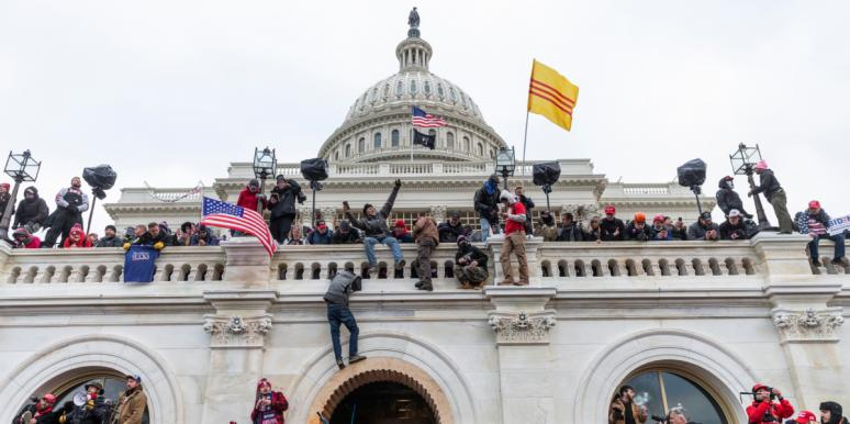 rioters climb the walls of the Capitol building on January 6, 2021