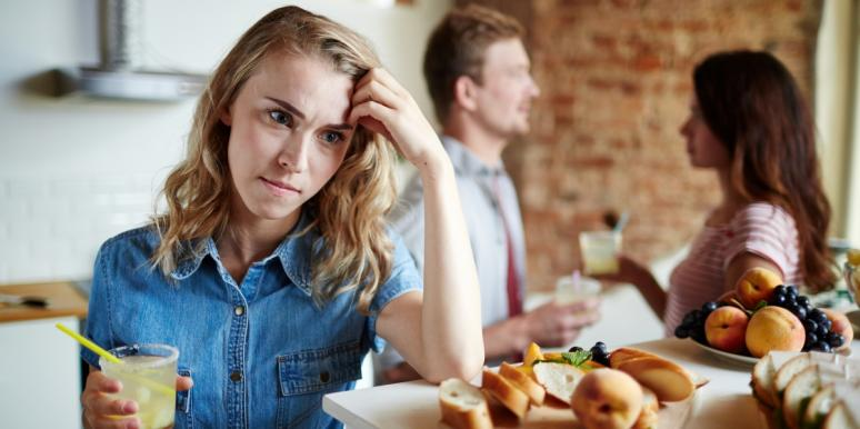 woman looking upset while man and woman talk behind her