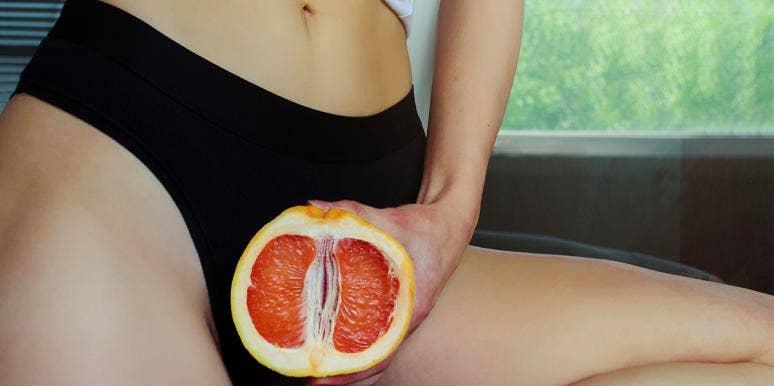 woman in black underwear holding grapefruit