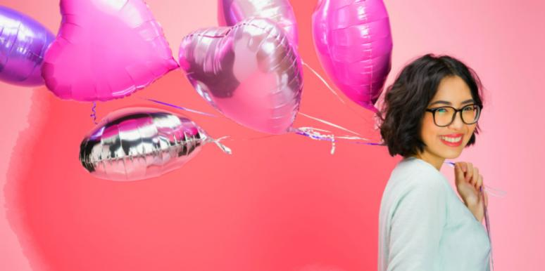 woman smiling holding heart balloons