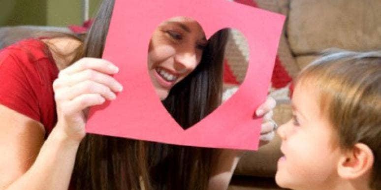 young woman peeking throught heart-shaped cutout at little boy