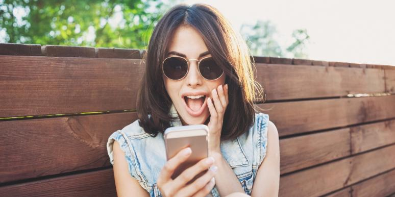 happy woman looking at her smartphone