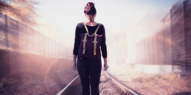 woman with backpack walking away on train tracks