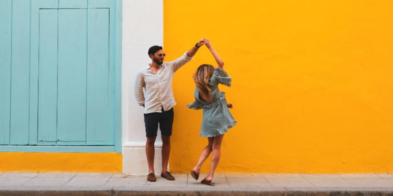 a couple dancing on the street yellow wall background
