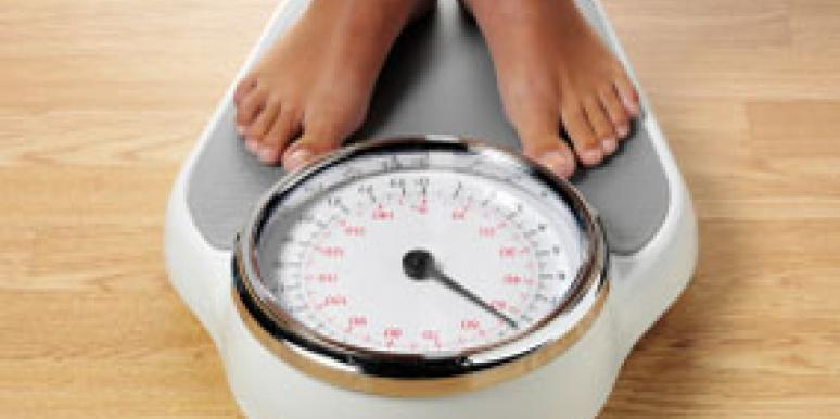woman standing on scale to check her weight