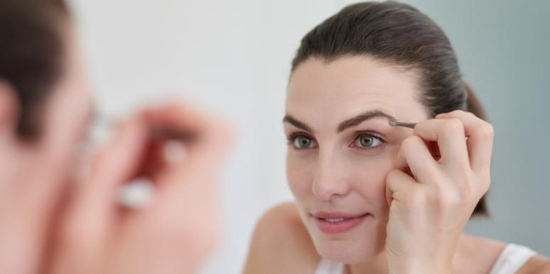 woman doing eyebrows in the mirror