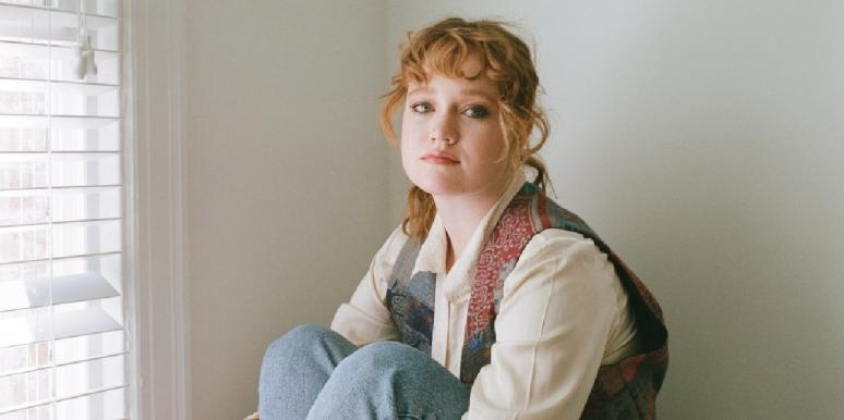 sad woman red hair in jeans staring forward