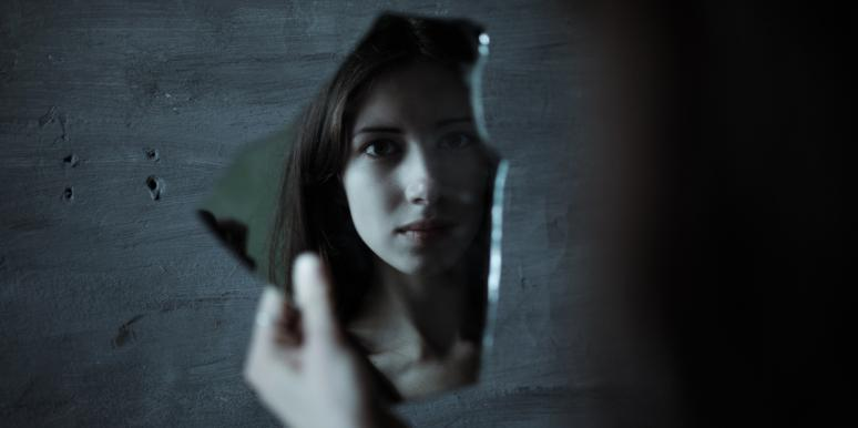 woman looking at broken mirror shard
