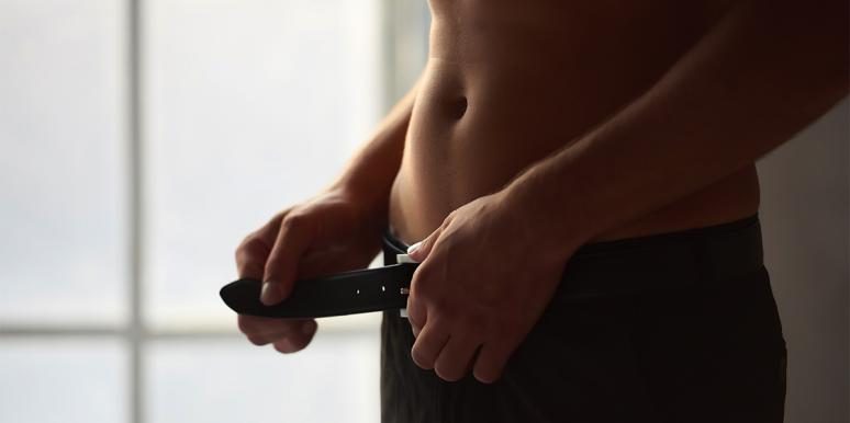 man unbuckling belt on pants