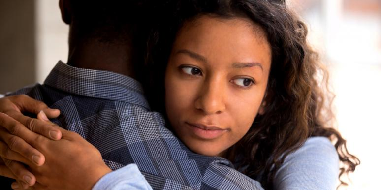 woman looking over man's shoulder not caring about relationship anymore